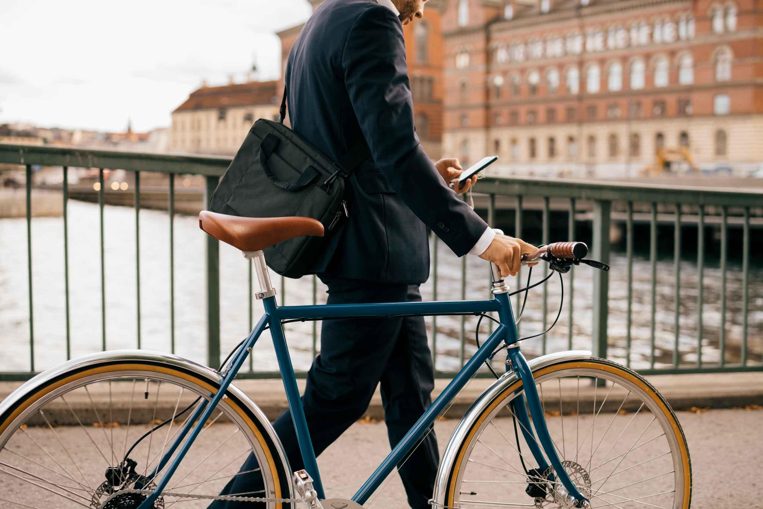 Image of business man pushing bicycle