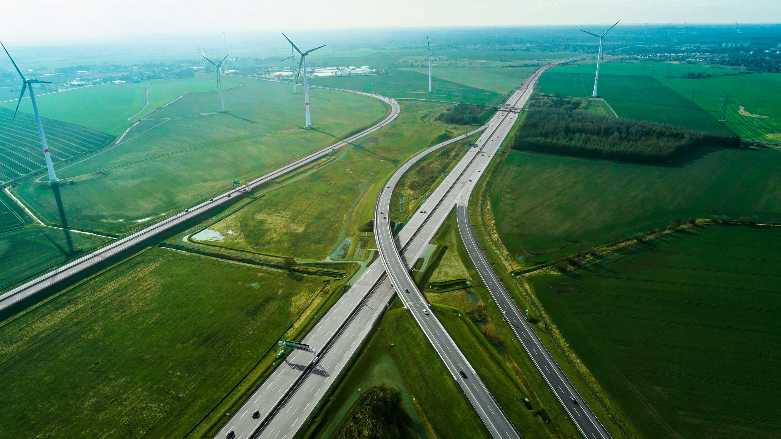 Image of road curving through fields containing wind turbines